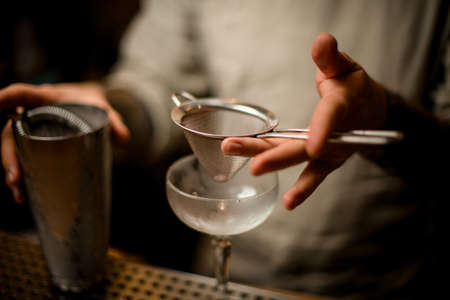 close-up on hand of bartender in which he holds sieve over wine glass Stock Photo