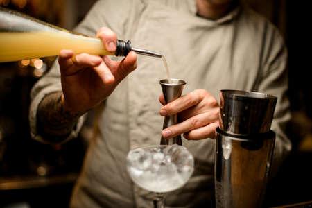 bartender carefully pours drink from bottle into metal jigger.