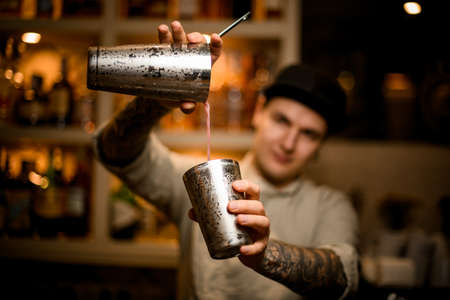 young barman holds shaker glasses in his hands and pours drink from them