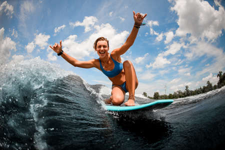 Cheerful woman riding on wave sitting on surfboard with raising arms