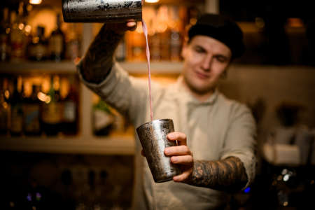 young barman holds shaker glasses in his hands and pours cocktail from them