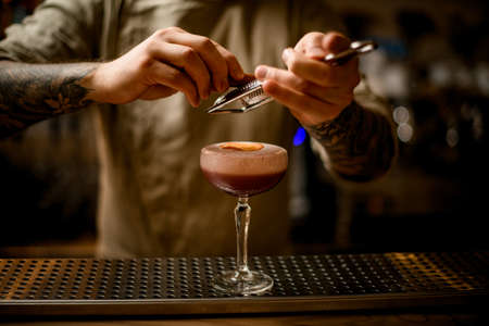 male bartender grates cinnamon over glass of cocktail with foam