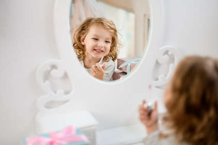 Reflection in mirror of little cheerful girl who paints her lips with lip gloss. Banque d'images