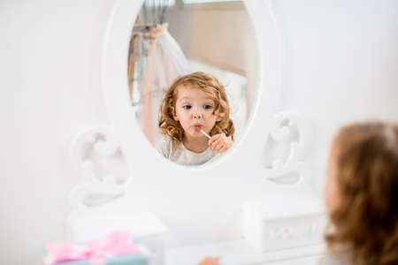 Reflection in round mirror of lovely little girl who paints her lips with lip gloss.