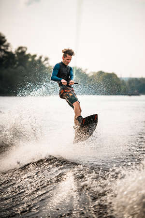young sportsman stands on wakeboard and actively rides on the splashing wave. Stock Photo