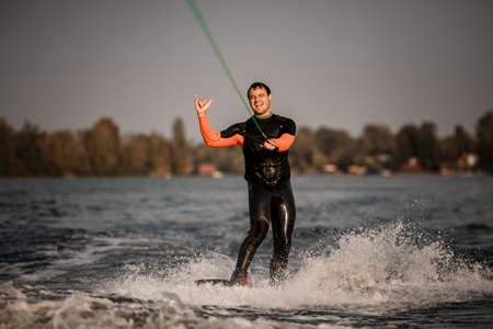 cheerful man shows gesture while riding along wave on wakeboard