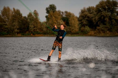 cheerful young man holding cable and rides wakeboard showing hand gesture.