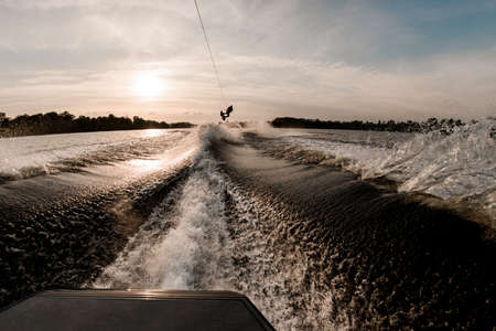 view of male wakeboarder doing jumping tricks on board on wave