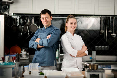 young man and woman chefs stand with crossed arms
