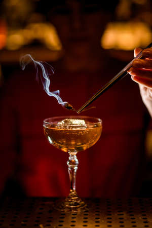 shiny glass with iced drink on bar and bartender holds smoldering plant over it Stock Photo
