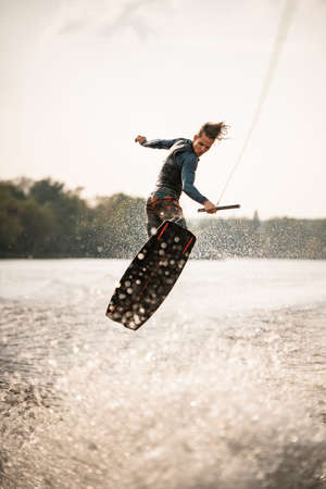 young athletic man jumps spectacularly on wakeboard above the water with splashes