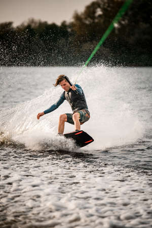 young sportsman in vest stands on wakeboard and ride down on the splashing wave.