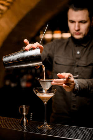 man bartender holds sieve and pours cocktail through it from shaker into glass