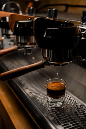 great view on glass with coffee on steel surface of professional coffee machine