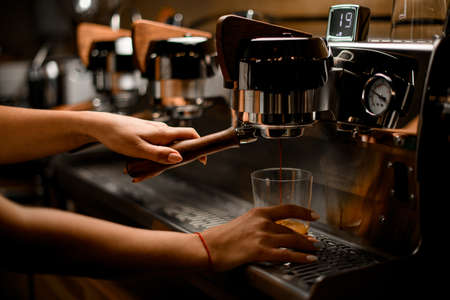 baristas hand controls lever of coffee machine that prepares and pours coffee into glass