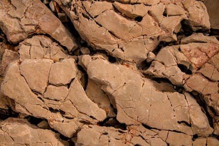 top view of brown stone coastline surface with cracks and erosion textures