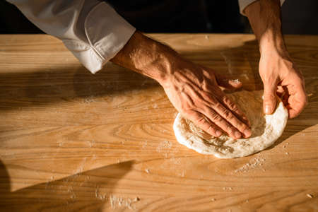Close-up view of male chefs hands who adjusts the dough on on wooden table.