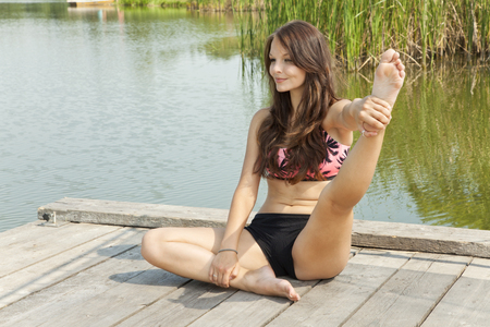Beautiful young woman stretching on the pier over the pond. Reklamní fotografie