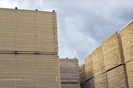 Lumber industry - finished lumber against sky. Machined wood planks deposited and stacked on heaps Imagens