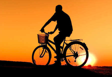 Man and  bike  silhouette in orange sunrise photo