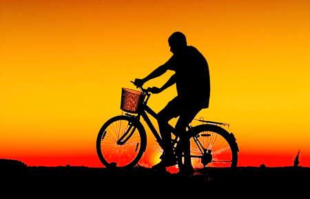 Man and  bike  silhouette in orange sunrise photo
