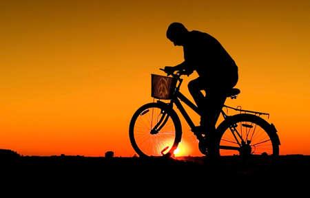 Man and  bike  silhouette in orange sunrise Stock Photo - 1261371