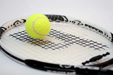 Tennis ball with a detailed racquet lying on it