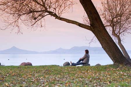 composure: Una giovane donna  donna � seduta e ha un rilassarsi sotto un albero