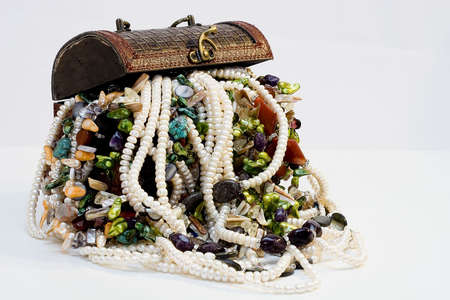 Chest full of jewelry treasures. Isolate on white photo