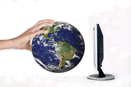 online internet presence: monitor and earth in hand Stock Photo