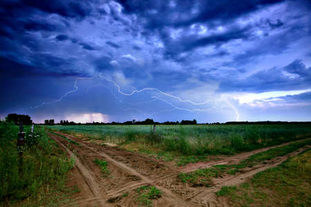 Rural road and dark storm clouds photo