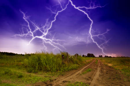 thunderclap: Rural road and lighting storm Stock Photo