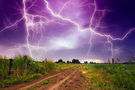 lightnings: Rural road and lighting storm Stock Photo