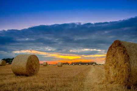 End of day over field with hay bale in Hungary- This photo make HDR Stockfoto