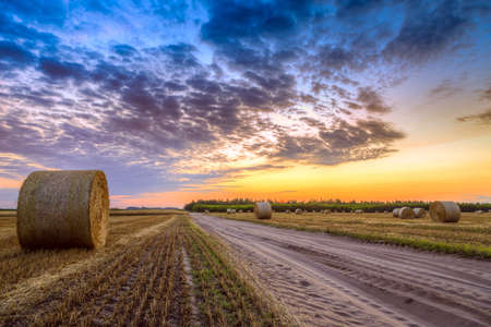 Sunset over rural road and farm field with hay bales photo
