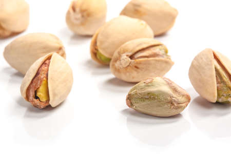 A mound of pistachio nuts on a white background photo
