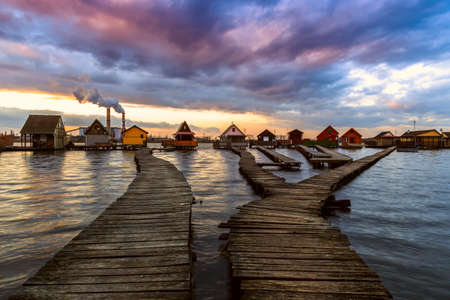 Sunset lake Bokod with pier and fishing wooden cottages, power plant in background, Hungary photo