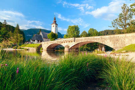 Church of Sv. John the Baptist and a bridge by the Bohinj lake, Slovenia photo