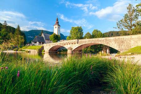 Church of Sv. John the Baptist and a bridge by the Bohinj lake, Slovenia photo