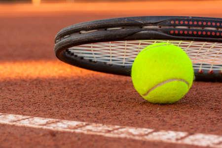racquet: Tennis ball and racquet on a tennis clay court Stock Photo