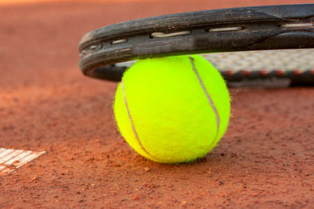 Tennis ball and racquet on a tennis clay court photo