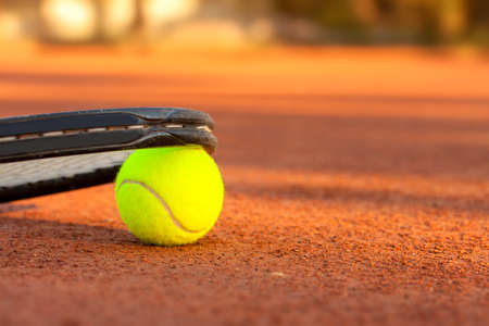 Tennis ball and racquet on a tennis clay court Stock Photo