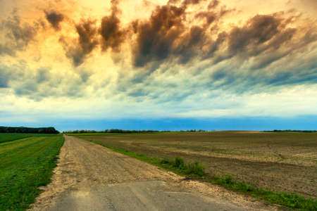 Summer landscape with green grass, road and clouds in Hungary photo