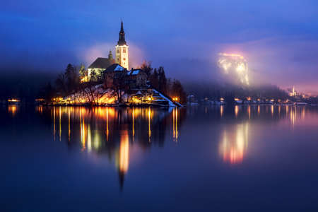 Foggy dusk in Bled lake in Slovenia photo