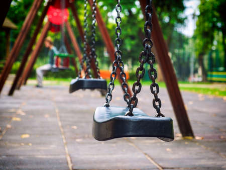 lonliness: Empty chain swing in playground in city
