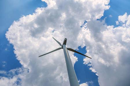 viento: solo ángulo bajo de la turbina de viento contra el cielo azul con nubes