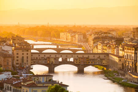 River Arno and famous bridge Ponte Vecchio at sunset in Florence, Tuscany, Italy