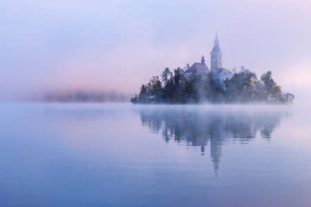 Misty morning in lake Bled and famous island with old church-Slovenia