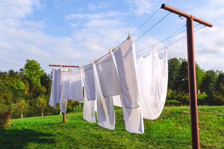 屋外の洗濯ラインで新鮮なきれいな白いシート乾燥
