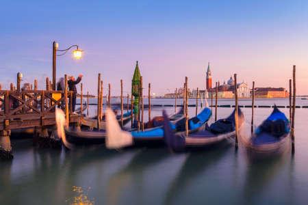 Venice with famous gondolas  in lagoon at sunrise as a background  can see the chucrh of San Giorgio Maggiore Archivio Fotografico